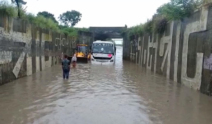 bus stuck underpass, passengers troubled, JCB helped